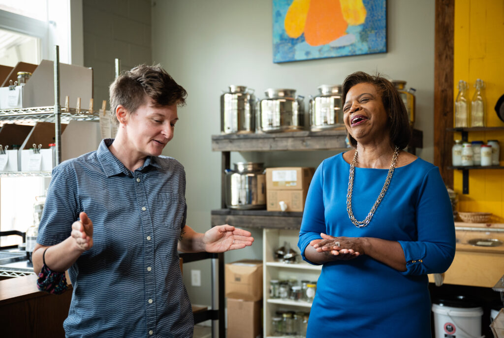 Cheri Beasley, right, a Democratic candidate for U.S. Senate, laughs with T Land, executive director of Part & Parcel, a package-free grocery store that employs neurodiverse individuals.